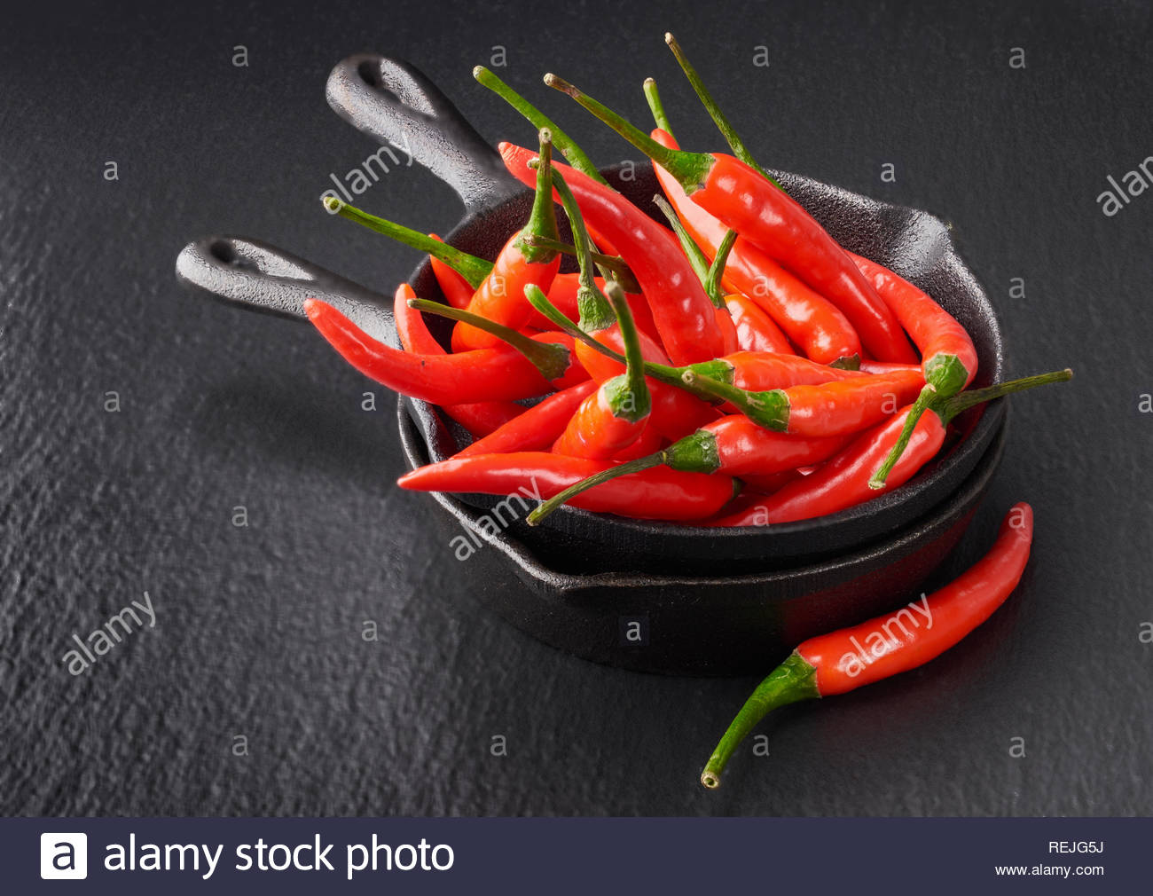 closeup-on-red-hot-chili-peppers-in-a-stack-of-two-grey-ceramic-bowls-on-black-slate-stone-background-REJG5J